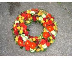 composition florale deuil couronne orange rouge